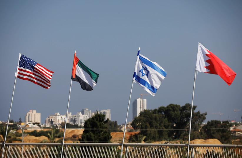 Las banderas de EE. UU., Emiratos Árabes Unidos, Israel y Bahrein ondean a lo largo de una carretera en Netanya (crédito de la foto: NIR ELIAS / REUTERS)