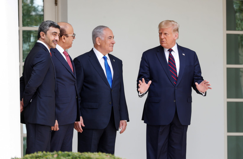 U.S. President Donald Trump speaks United Arab Emirates (UAE) Foreign Minister Abdullah bin Zayed, Bahrain's Foreign Minister Abdullatif Al Zayani and Israel's Prime Minister Benjamin Netanyahu prior to signing the Abraham Accords, normalizing relations between Israel and some of its Middle East nei (photo credit: REUTERS/TOM BRENNER)