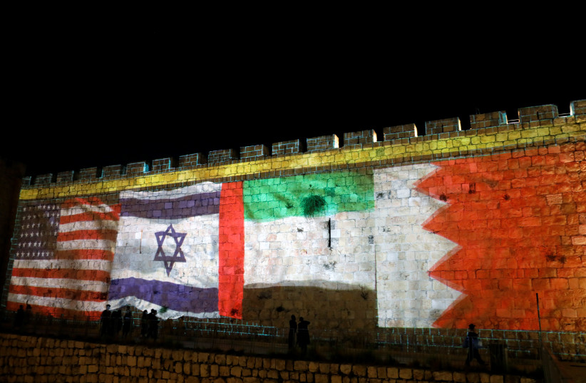The flags of the United States, Israel, United Arab Emirates and Bahrain are projected on a section of the walls surrounding Jerusalem's Old City. September 15, 2020 (photo credit: RONEN ZVULUN / REUTERS)
