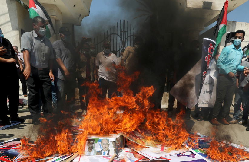 Palestinians burn pictures depicting Abu Dhabi Crown Prince Mohammed bin Zayed al-Nahyan, Israeli Prime Minister Benjamin Netanyahu and U.S. President Donald Trump during a protest against the United Arab Emirates and Bahrain's deal with Israel to normalise relations, in Gaza City September 15, 2020 (photo credit: REUTERS/MOHAMMED SALEM)