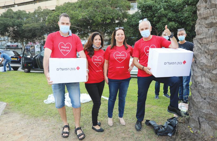BANK HAPOALIM'S (from left) Roni Garfunkel, Naama Halevi-Peer, Ronit Meiri and Ofer Semo deliver food packages for Rosh Hashanah, September 2020  (photo credit: AVIV GOTTLIEB)