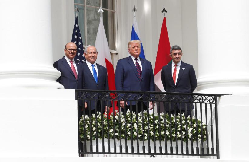 Abdullatif Al Zayani, Benjamin Netanyahu, Donald Trump, and Abdullah bin Zayed sign the Abraham Accords (photo credit: REUTERS/TOM BRENNER)