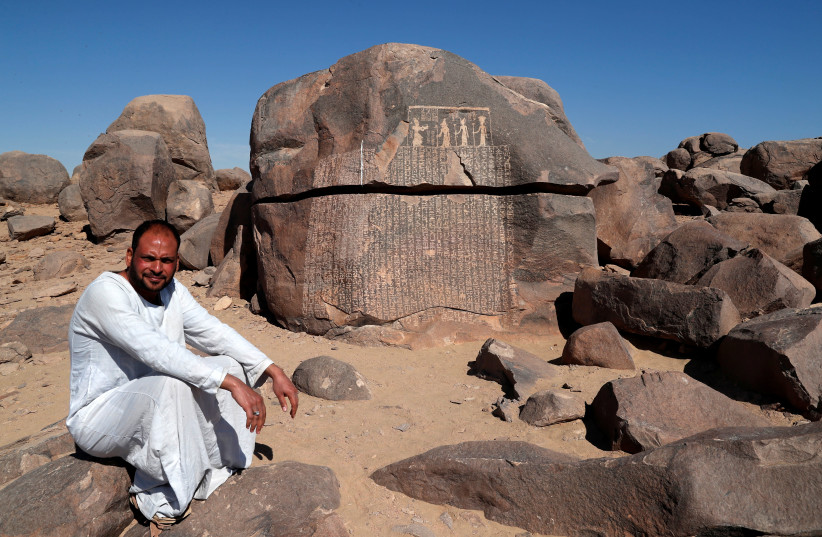 "Ayman Hussien, a guard of Famine Stela, or ""Rock of Starvation"", sits near the rock, initially attributed to the reign of King Djoser (Third Dynasty), during a shortage of the Nile flood that led to a seven-year drought and famine, on the Nile's Sehel Island at Aswan, Egypt February 21, 2020 (photo credit: REUTERS/AMR ABDALLAH DALSH)"