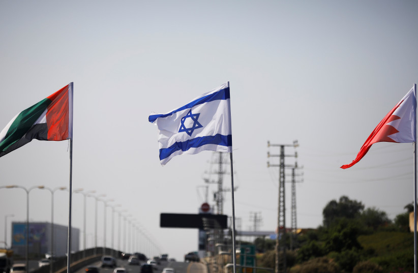 The flags of the United Arab Emirates, Israel and Bahrain flutter along a road in Netanya, Israel September 14, 2020 (photo credit: REUTERS/NIR ELIAS)