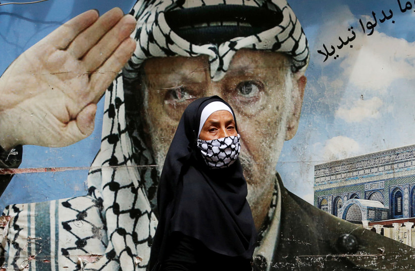 Une femme passe devant une affiche représentant le défunt dirigeant palestinien Yasser Arafat, camp de réfugiés palestiniens de Chatila, Beyrouth (crédit photo: MOHAMED AZAKIR / REUTERS)
