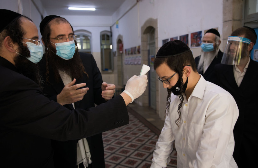 A teacher checks the temperature of a student at a haredi Orthodox school in Jerusalem, May 6, 2020 (photo credit: NATI SHOHAT/FLASH90)