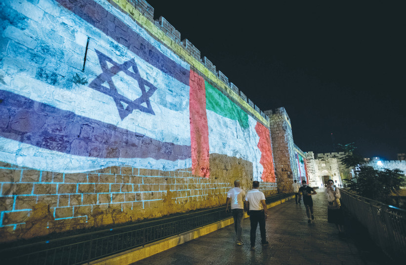 The flags of the United Arab Emirates, Israel and Bahrain are screened on the walls of Jerusalem's Old City on September 15. (photo credit: YONATAN SINDEL/FLASH90)