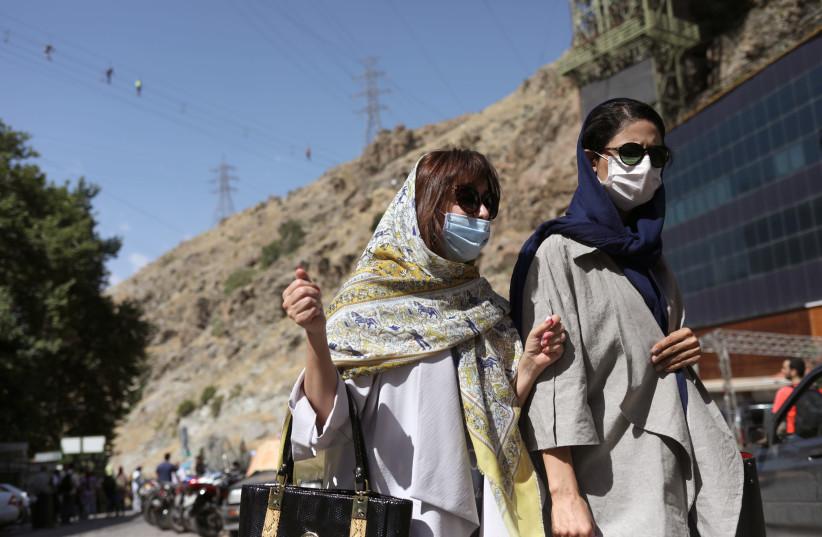 Iranian women wearing protective face masks walk in Darband street, following the outbreak of the coronavirus disease (COVID-19), in Tehran, Iran June 12, 2020 (photo credit: ALI KHARA/WANA (WEST ASIA NEWS AGENCY)/VIA REUTERS)