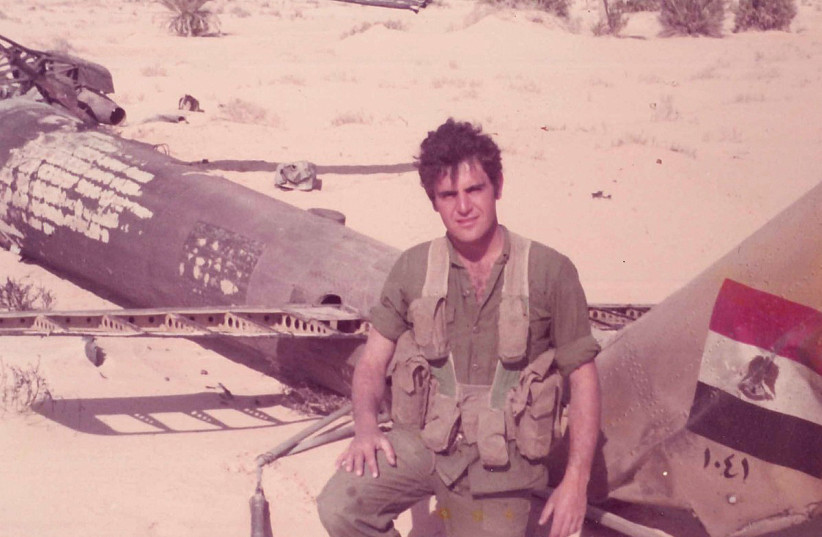The author next to a downed Egyptian helicopter during the Yom Kippur War. (photo credit: Courtesy)