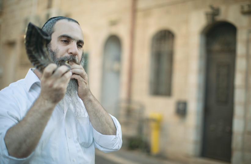 AN ULTRA-ORTHODOX man watches protesters march across Jerusalem's 'Bridge of Strings' in August.  (photo credit: REUTERS)