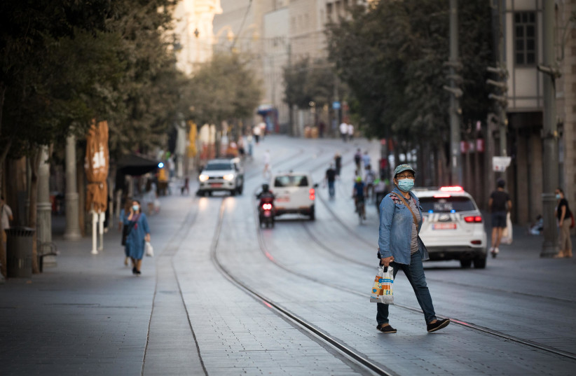 People walk next to closed shops on Jaffa Street in downtown Jerusalem on September 24, 2020, during a nationwide lockdown (photo credit: YONATHAN SINDEL/FLASH90)