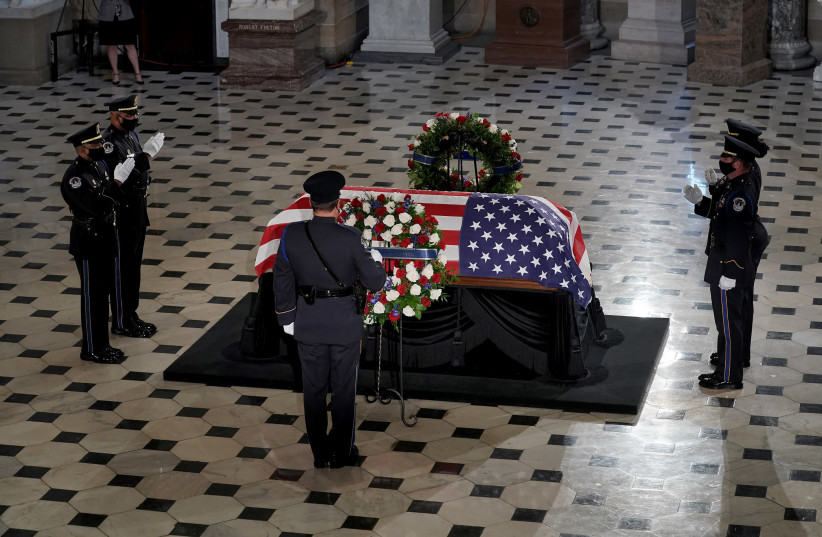 A U.S. Capitol Police honor guard salutes as U.S. Supreme Court Associate Justice Ruth Bader Ginsburg's flag-draped casket lies in state in Statuary Hall at the Capitol, Washington, U.S., September 25, 2020 (photo credit: GREG NASH/POOL VIA REUTERS)