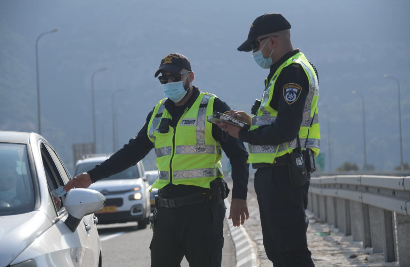 Police check the ID of a driver, at a checkpoint put in place during Israel's second lockdown, September 2020. (photo credit: AVSHALOM SASSONI/ MAARIV)
