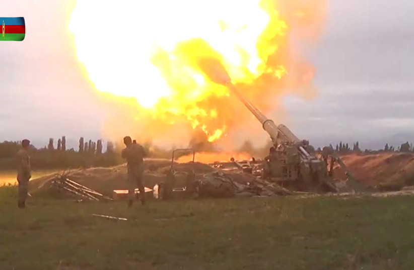 A still image from a video released by the Azerbaijan's Defence Ministry shows members of Azeri armed forces firing artillery during clashes between Armenia and Azerbaijan over the territory of Nagorno-Karabakh in an unidentified location, in this still image from footage released September 28, 2020 (photo credit: DEFENCE MINISTRY OF AZERBAIJAN/HANDOUT VIA REUTERS)