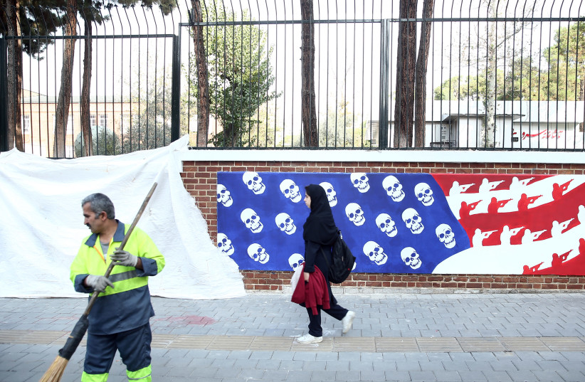 A woman walks in front of new murals of the former US embassy in Tehran, Iran November 2, 2019 (photo credit: REUTERS)