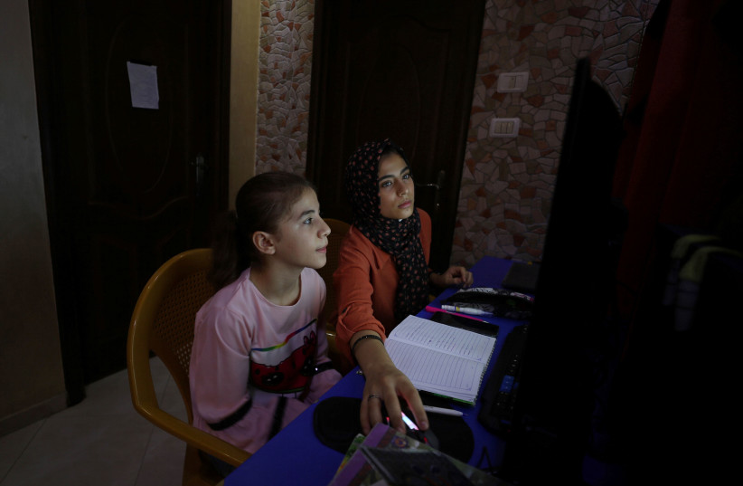 Palestinian sisters Raseel and Mariam Hussein attend their online lessons in their home, amid the coronavirus disease (COVID-19) outbreak, in Gaza City September 22, 2020. (photo credit: MOHAMMED SALEM/ REUTERS)
