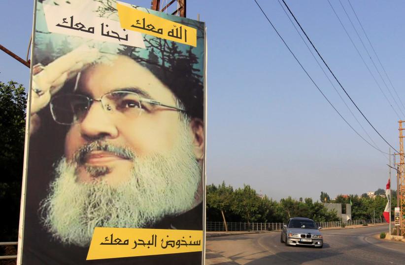 A car drives past a poster depicting Lebanon's Hezbollah leader Sayyed Hassan Nasrallah in Adaisseh village, near the Lebanese-Israeli border, Lebanon July 28, 2020. (photo credit: AZIZ TAHER/REUTERS)
