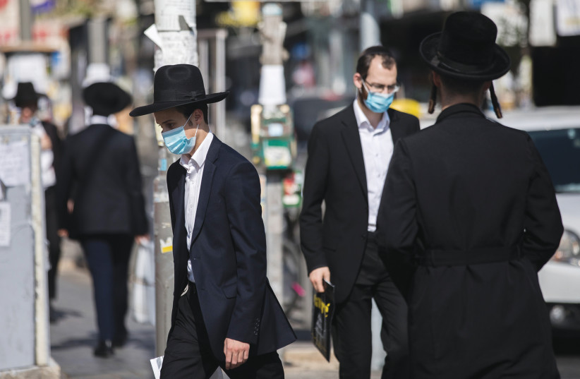Ultra-Orthodox residents walk through of the Mea She'arim neighborhood of Jerusalem, August 2020 (photo credit: YONATAN SINDEL/FLASH90)
