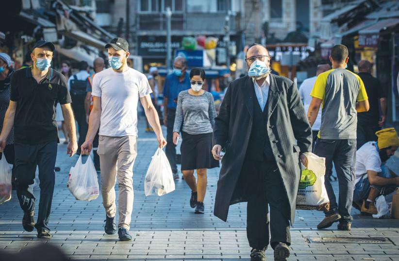 PEOPLE WALK through the Mahaneh Yehuda market in Jerusalem on Wednesday. (photo credit: OLIVIER FITOUSSI/FLASH90)