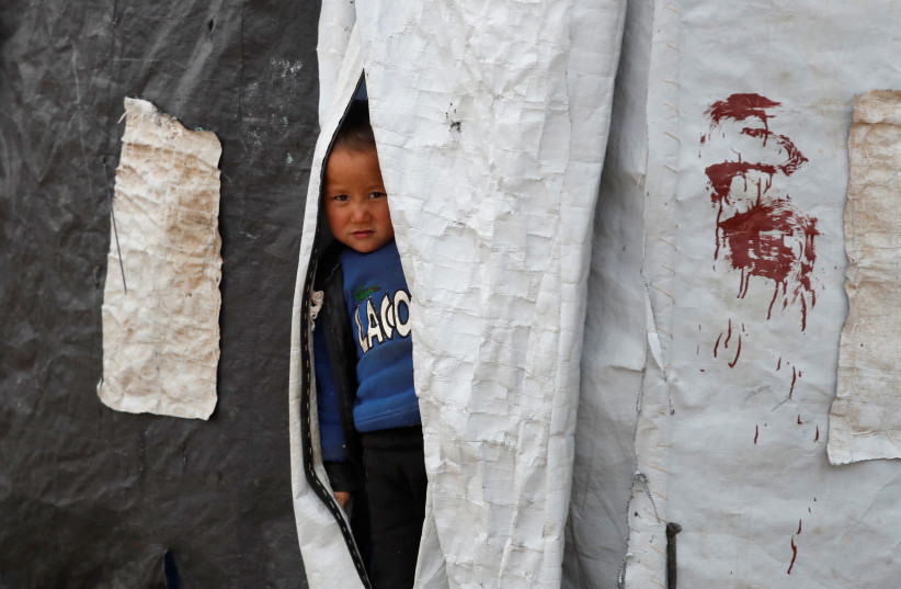 A boy looks out from inside a tent in al-Roj camp, Syria, January 10, 2020. (photo credit: GORAN TOMASEVIC/REUTERS)