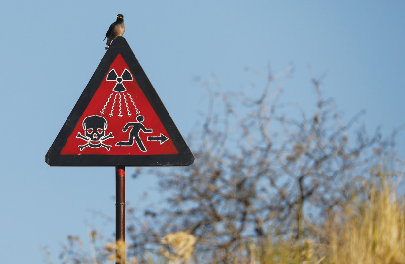 A BIRD SITS on a radiation sign at the uranium ore dump near the town of Mailuu-Suu, Kyrgyzstan. (photo credit: PAVEL MIKHEYEV/REUTERS)