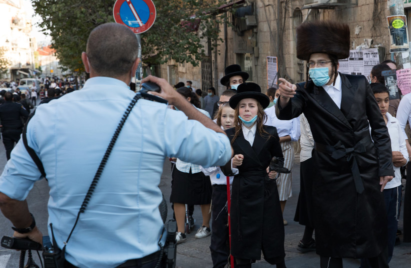 Israeli police officers clash with Ultra Orthodox Jewish men during a protest against the enforcement of coronavirus emergency regulations, in the Ultra Orthodox jewish neighborhood of Mea Shearim, Jerusalem, October 4, 2020 (photo credit: NATI SHOHAT/FLASH90)