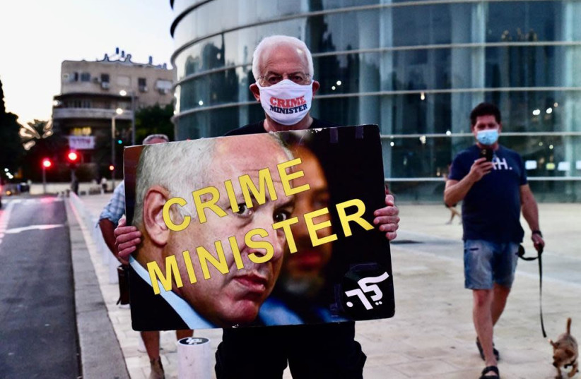 "A protester holds a sign that reads, ""Crime Minister,"" during demonstrations held against Prime Minister Benjamin Netanyahu. October, 10, 2020. (photo credit: AVSHALOM SASSONI/ MAARIV)"