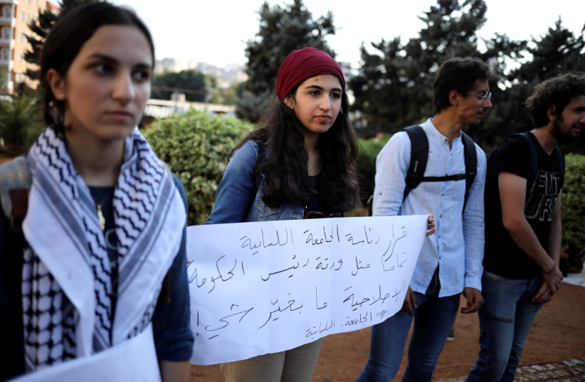 Zainab Sharaf al-Deen, 18, is seen holding a placard alongside others at an anti-government protest in Beirut, Lebanon, on October 22, 2019. (photo credit: ALKIS KONSTANTINIDIS / REUTERS)