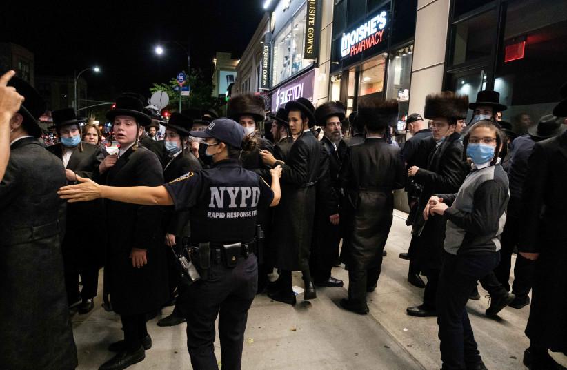 Un officier du NYPD s'entretient avec des juifs ultra-orthodoxes alors qu'ils se rassemblent dans le quartier Borough Park de Brooklyn au milieu de l'épidémie de coronavirus à New York, États-Unis, le 7 octobre 2020 (crédit photo: REUTERS / YUKI IWAMURA)