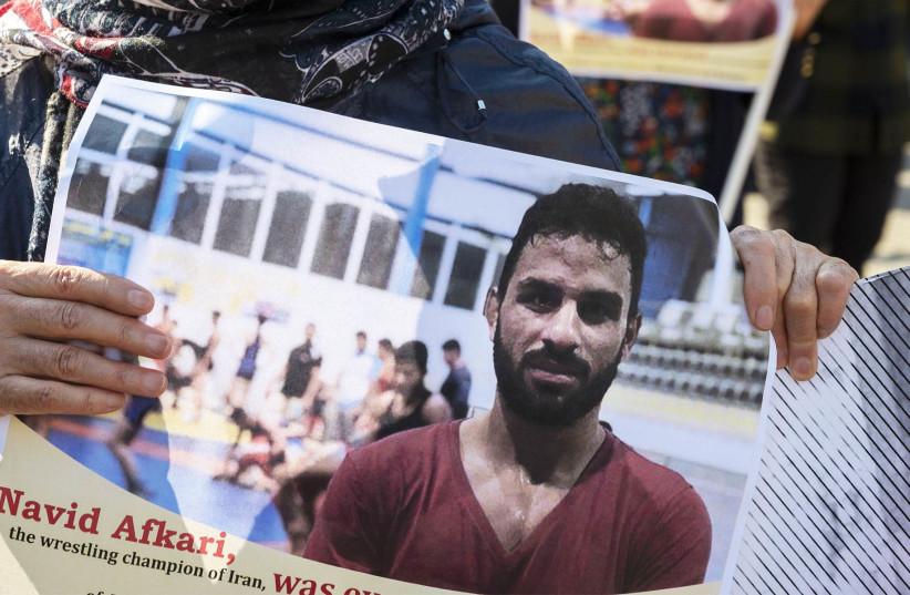 A portrait of Iranian wrestler Navid Afkari during a demonstration on the Dam Square in Amsterdam, Sept. 13, 2020.  (photo credit: EVERT ELZINGA/ANP/AFP VIA GETTY IMAGES)