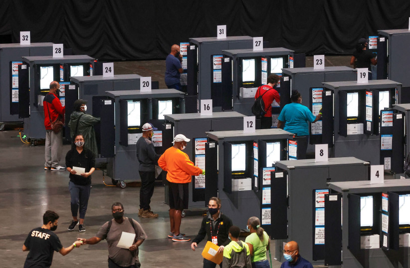 People cast their ballots during early voting for the upcoming presidential elections inside of The Atlanta Hawks' State Farm Arena in Atlanta, Georgia, US, October 12, 2020 (photo credit: CHRIS ALUKA BERRY/ REUTERS)