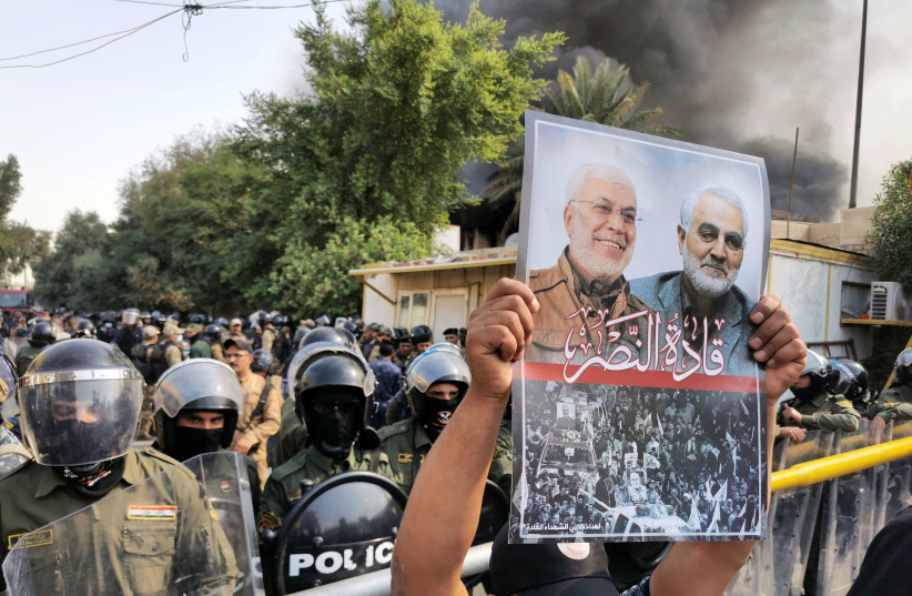 A supporter of Hashid Shaabi holds a picture of late Quds Force commander Qasem Soleimani and Iraqi militia commander Abu Mahdi al-Muhandis during a protest in Baghdad, Iraq, October 17, 2020 (photo credit: REUTERS/THAIER AL-SUDANI)