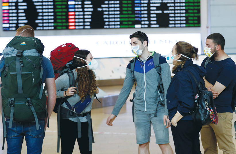 Travelers at Ben-Gurion Airport in March - to bring tourists back to Israel is not an act of lunacy. (photo credit: RONEN ZVULUN / REUTERS)