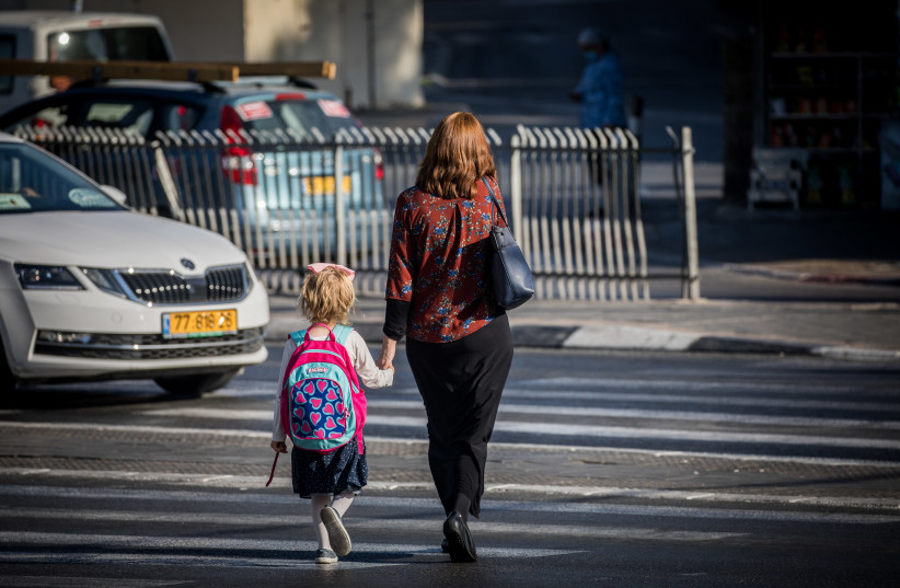 An ultra-Orthodox woman accompanies her daughter to school, Jerusalem, October 19, 2020 (photo credit: YONATAN SINDEL/FLASH90)