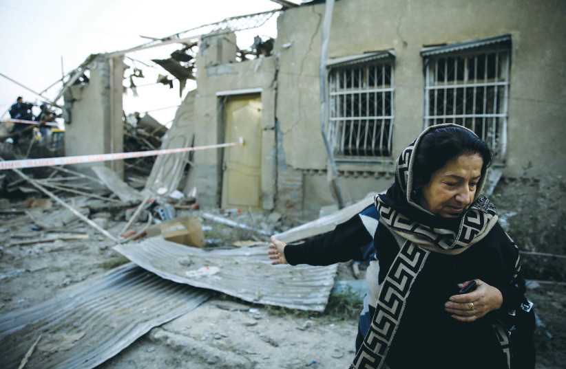 HICRAN QULIYEVA stands in front of her house in Ganja, Azerbaijan, on Saturday, after it was hit by a rocket during the fighting over Nagorno-Karabakh.  (photo credit: REUTERS)