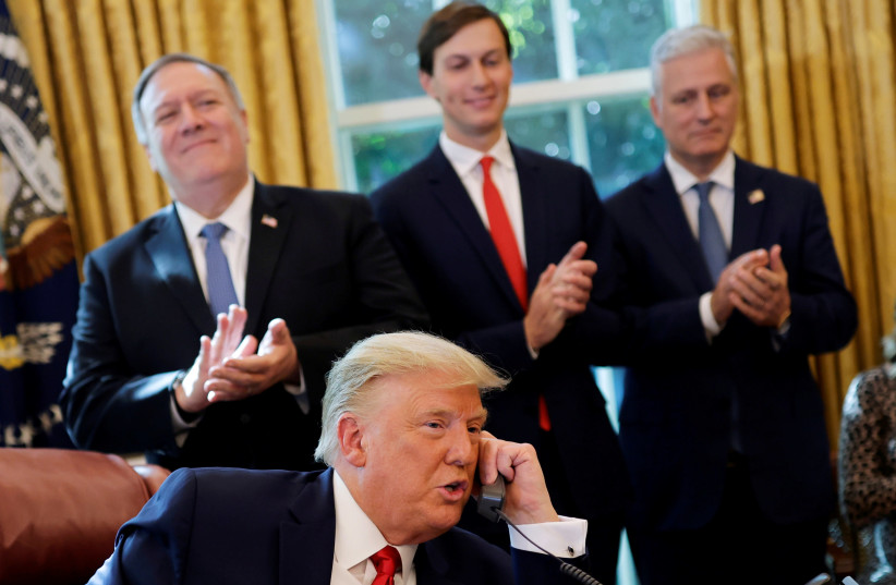 Secretary of State Mike Pompeo and White House senior advisor Jared Kushner applaud as US President Donald Trump is seen on the phone with leaders of Israel and Sudan, in the Oval Office at the White House in Washington, October 23, 2020. (photo credit: CARLOS BARRIA / REUTERS)