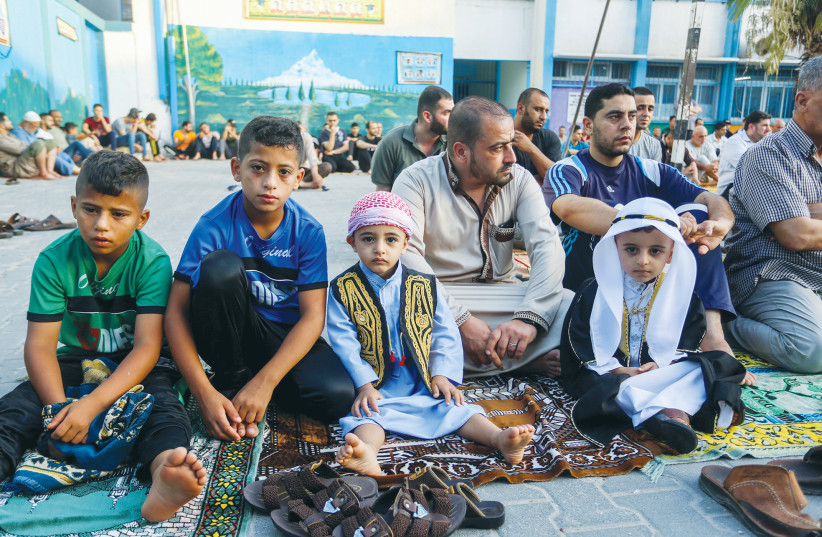 MEN AND boys attend a prayer in July to mark the Muslim holiday of Eid al-Adha, at an UNRWA school in Rafah, in the southern Gaza Strip.  (photo credit: ABED RAHIM KHATIB/FLASH90)