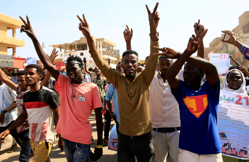 Sudanese protesters chant slogans as they gather ahead of a rally to put pressure on the government to improve conditions and push ahead with reform in Khartoum, Sudan October 21, 2020. (photo credit: REUTERS/ MOHAMED NURELDIN ABDALLAH)