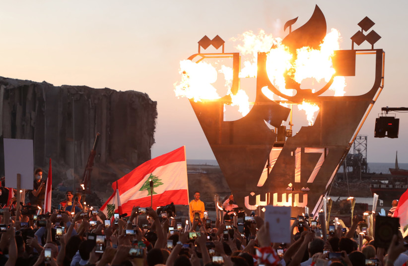 """Anti-government demonstrators take pictures of a metal sculpture spelling out """"revolution"""" topped by flames. (photo credit: MOHAMED AZAKIR / REUTERS)"""