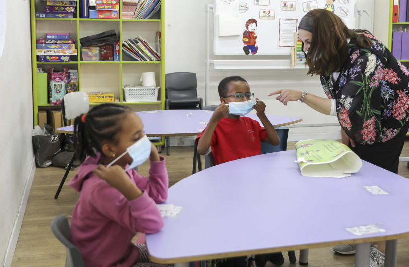 A teacher instructs students in proper mask wear, as first through fourth graders return to school, November 1, 2020. (photo credit: MARC ISRAEL SELLEM)