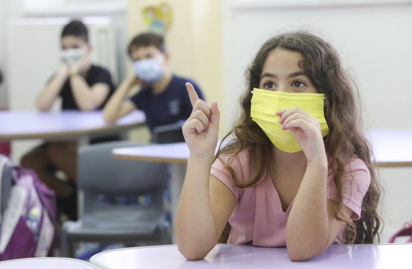A masked student raises her hand on her first day back in school, November 1, 2020.  (photo credit: MARC ISRAEL SELLEM)