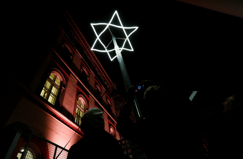 People take pictures of a light symbol, marking the place where Viennese synagogues once stood before they were destroyed, after a ceremony to mark the 80th anniversary of Kristallnacht, also known as Night of Broken Glass, in front of a then destroyed Synagogue in Vienna, Austria November 8, 2018. (photo credit: REUTERS)