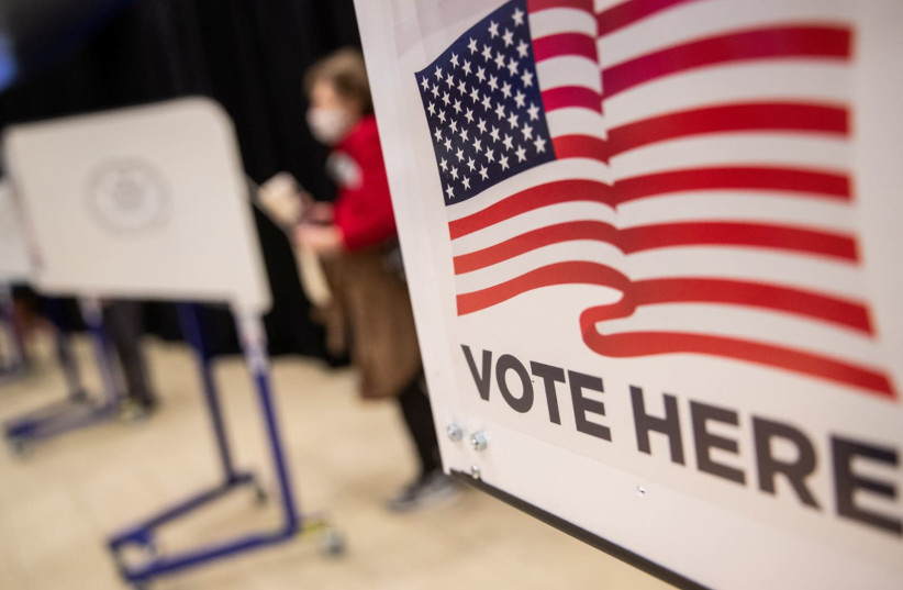 An American flag sign is seen on a voting booth at Madison Square Garden, which is used as a polling station on the first day of early voting in Manhattan, New York, U.S. October 24, 2020. (photo credit: REUTERS/JEENAH MOON)