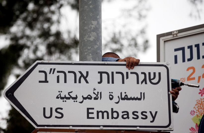 A worker hangs a road sign directing to the U.S. embassy, in the area of the U.S. consulate in Jerusalem, May 7, 2018.  (photo credit: REUTERS)