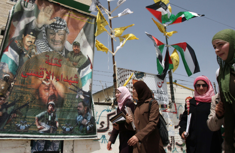 Palestinian students walk past a Fatah poster at the Palestine Polytechnic University in Hebron (photo credit: REUTERS)