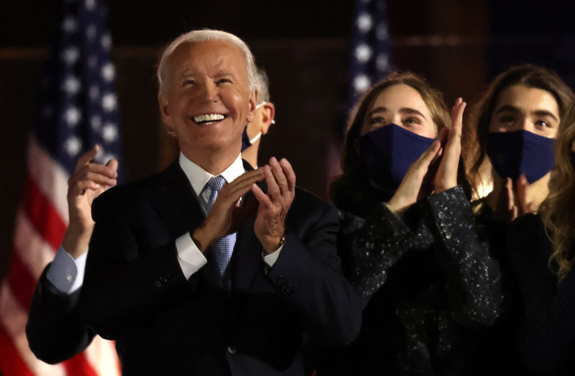 Democratic 2020 U.S. presidential nominee Joe Biden applauds next to his granddaughters after speakig during his election rally, after news media announced that he has won the 2020 U.S. presidential election, in Wilmington, Delaware, U.S., November 7, 2020. (photo credit: JONATHAN ERNST / REUTERS)