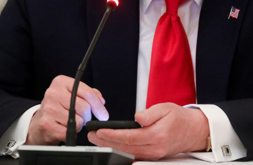 US President Donald Trump taps the screen on a mobile phone at the approximate time a tweet was released from his Twitter account, during a roundtable discussion on the reopening of small businesses in the State Dining Room at the White House in Washington, US, June 18, 2020. (photo credit: REUTERS/LEAH MILLIS/FILE PHOTO)