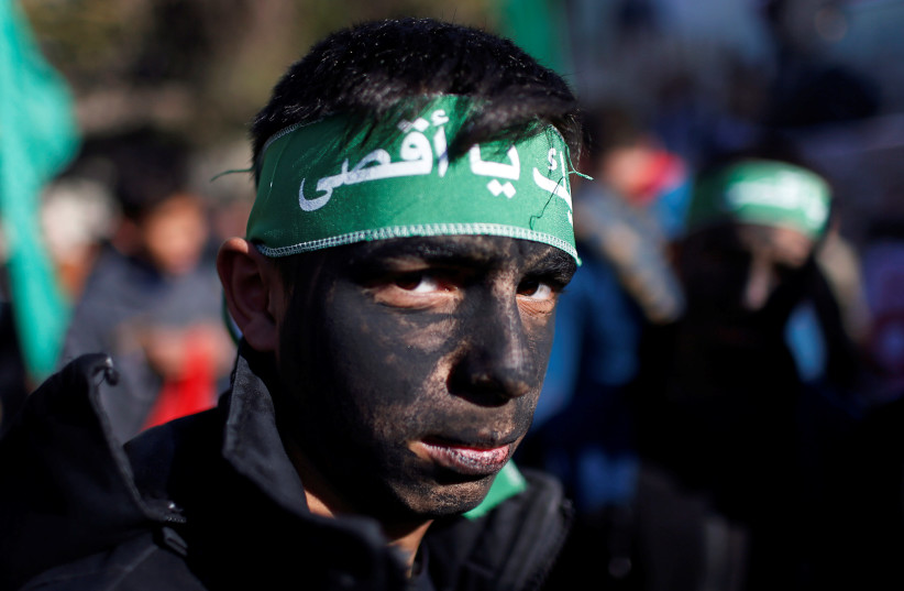 A young Palestinian has his face painted as he looks on during a Hamas rally in Gaza January 3, 2020 (photo credit: REUTERS/MOHAMMED SALEM)