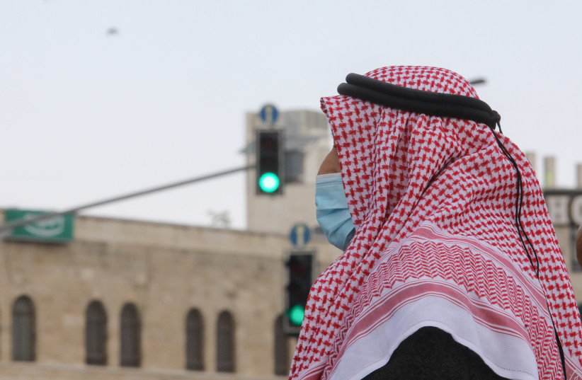 An Arab man wears a medical mask amid the coronavirus pandemic. (photo credit: MARC ISRAEL SELLEM)