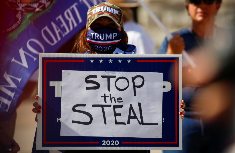 """A supporter of President Donald Trump holds a sign during a """"Stop the Steal"""" protest after the 2020 US presidential election was called by the media for Democratic candidate Joe Biden, in front of the Arizona State Capitol in Phoenix, Arizona, US, November 7, 2020 (photo credit: REUTERS/JIM URQUHART)"""